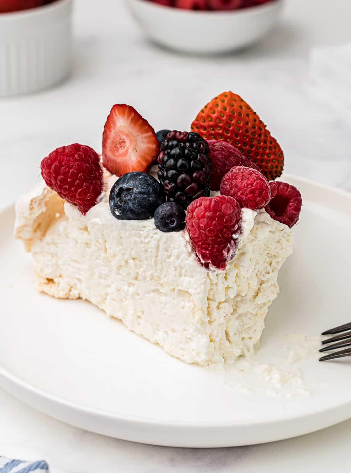 Bite taken out of slice of Pavlova on white plate