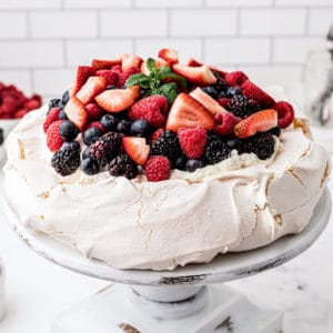 Square photo of Pavlova on cake stand topped with whipped cream and fruit