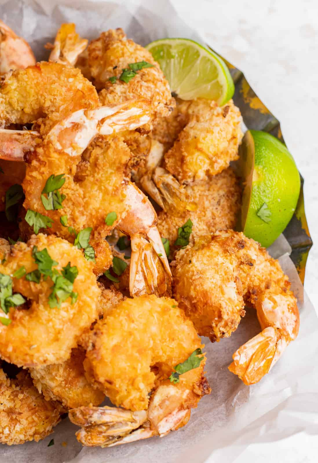 Overhead of Coconut Shrimp in basket with limes
