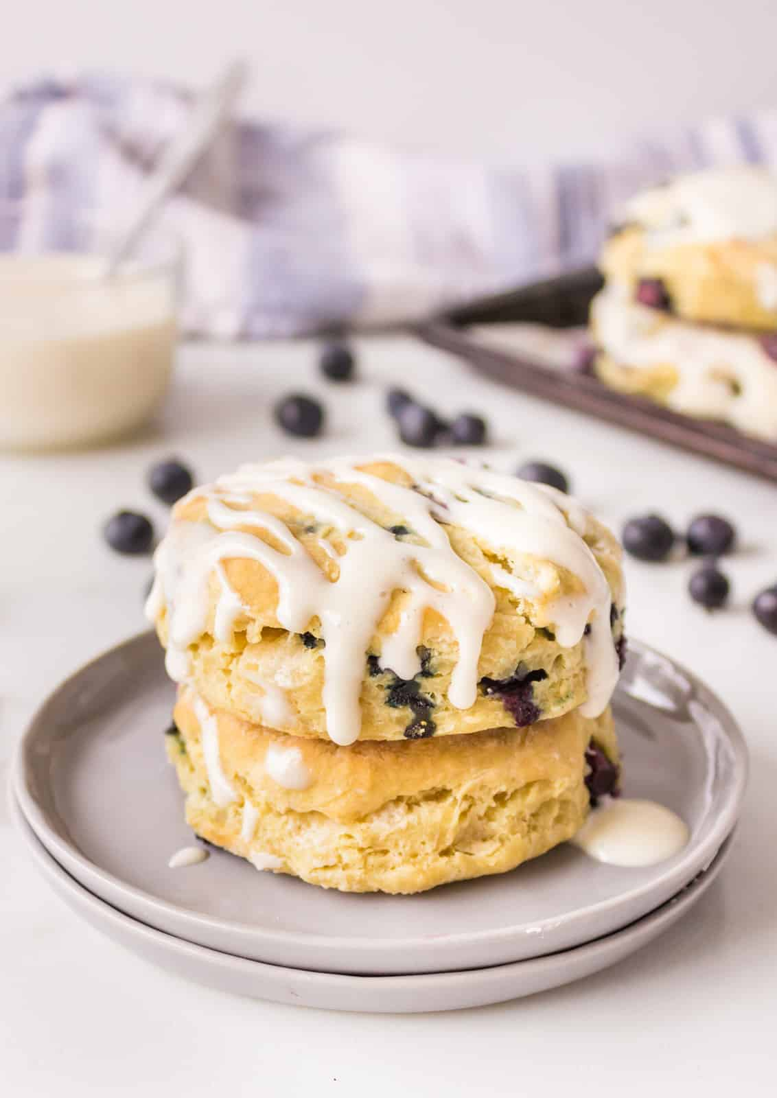 Two stacked Blueberry Biscuits on plate with icing on top