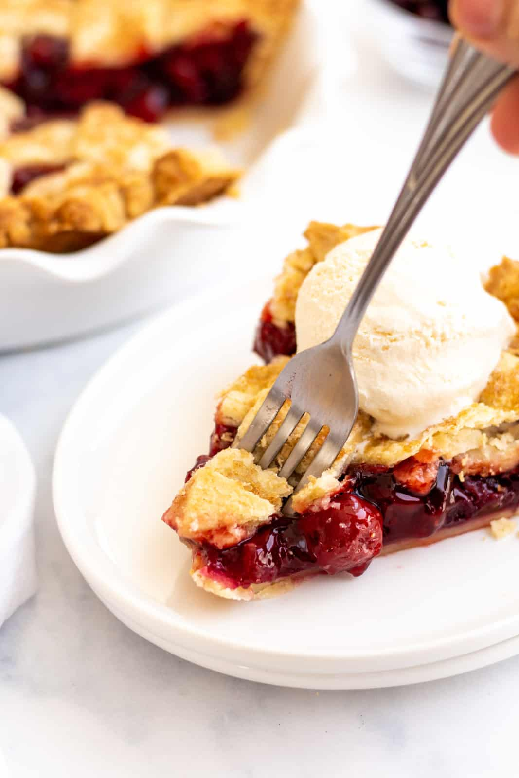 Fork going into slice of Cherry Pie Recipe on white plate