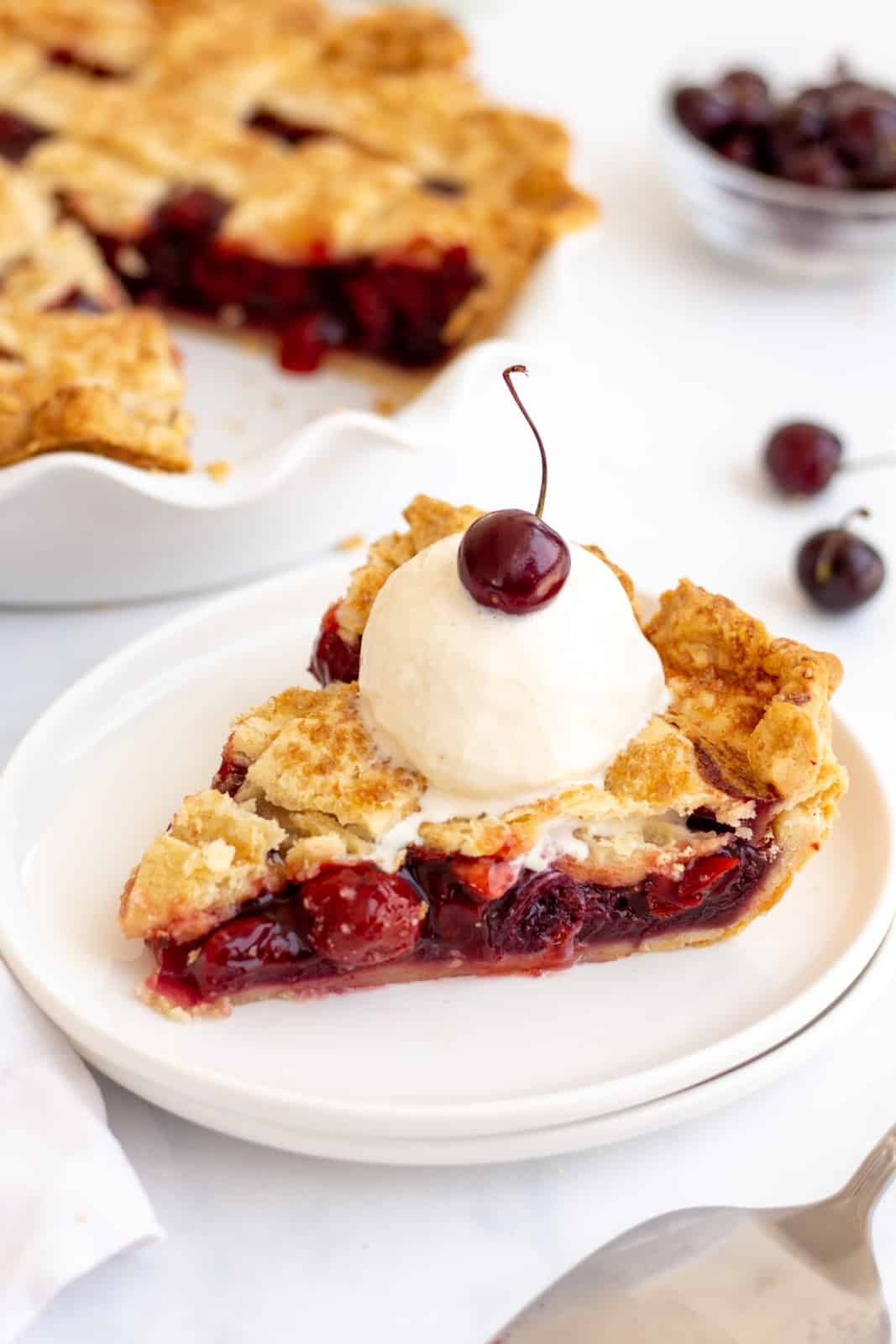 Slice of Cherry Pie on white plate topped with ice cream and cherry
