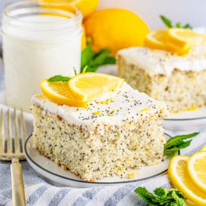 Square image of a slice of cake o white plate topped with lemon and mint