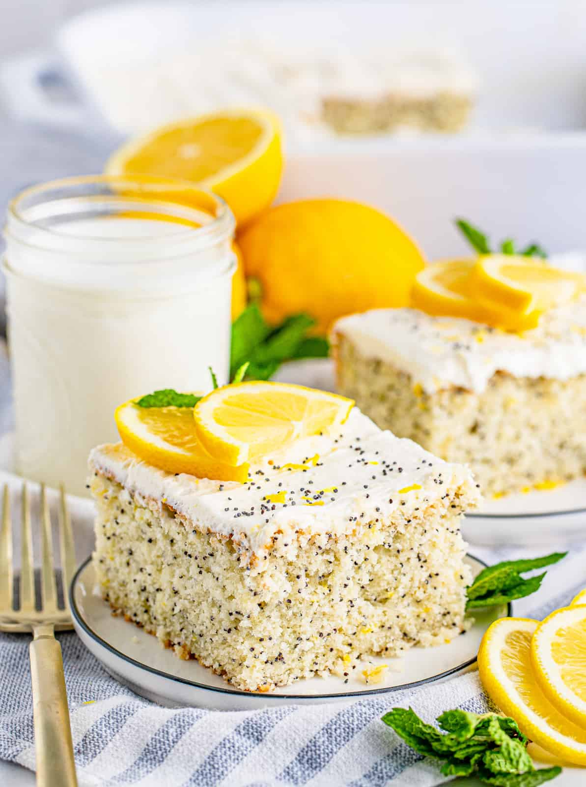 Two slices of The Best Lemon Poppy Seed Cake topped with lemon and mint