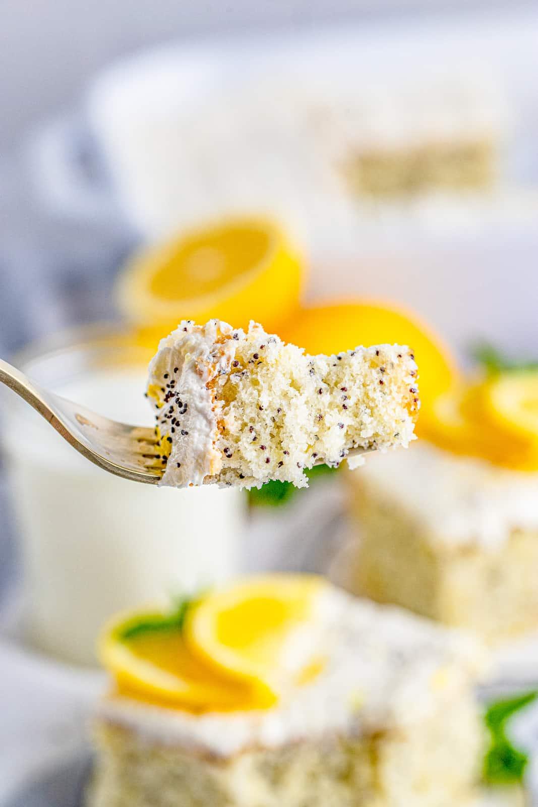 Fork holding up a bite of Lemon Poppy Seed Cake