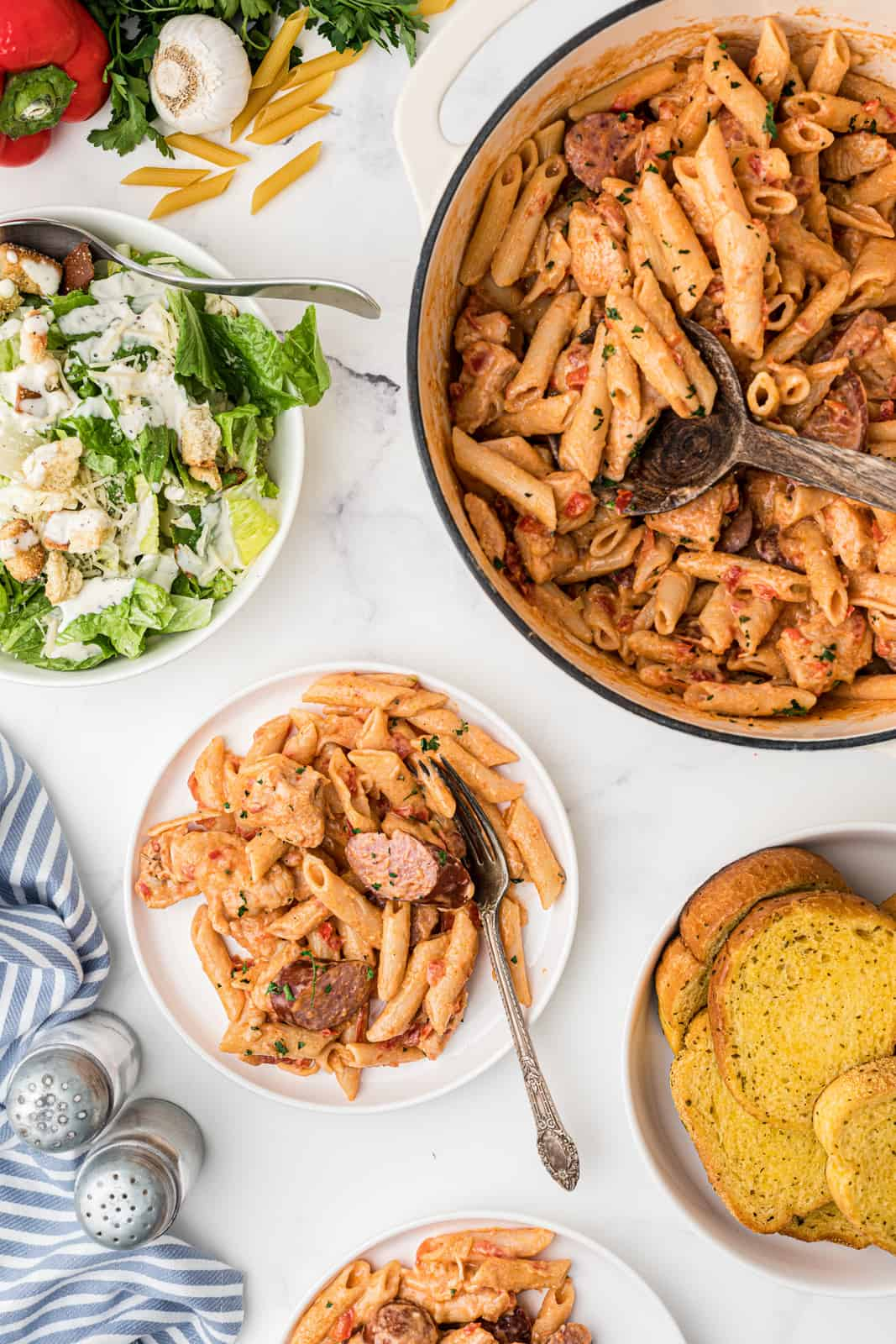 Overhead of Cajun Pasta Recipe in dutch oven and on plate with side salad