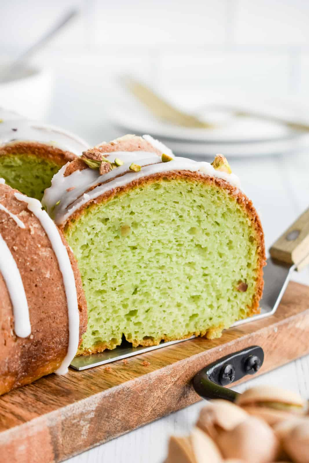 Cake server pulling out a slice of Pistachio Cake