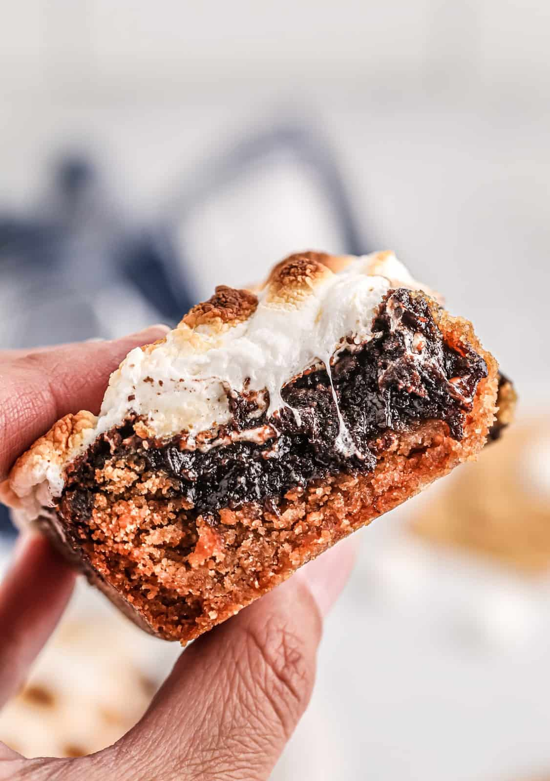 Hand holding up one S'mores Bar Recipe showing layers