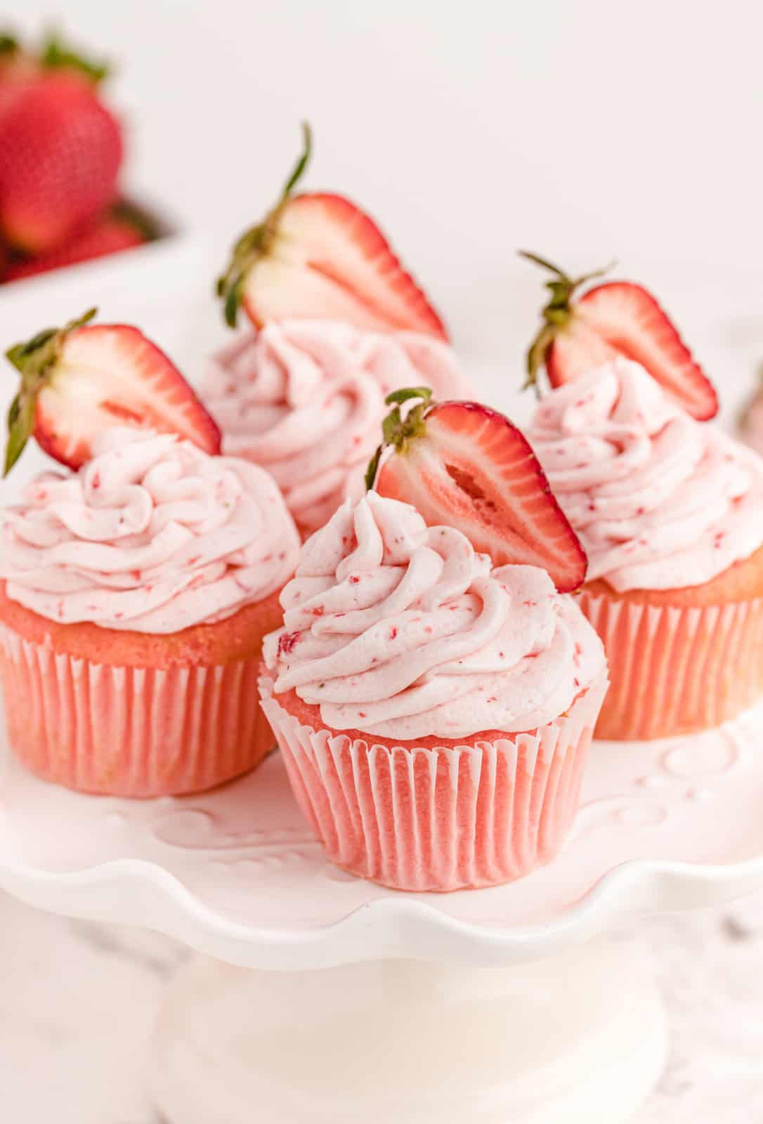 Four Strawberry Cupcakes on cake stand topped with strawberries