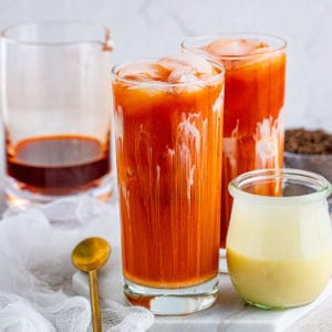 Square photo of two glasses of Thai Iced Tea with spoon and sweetened condensed milk