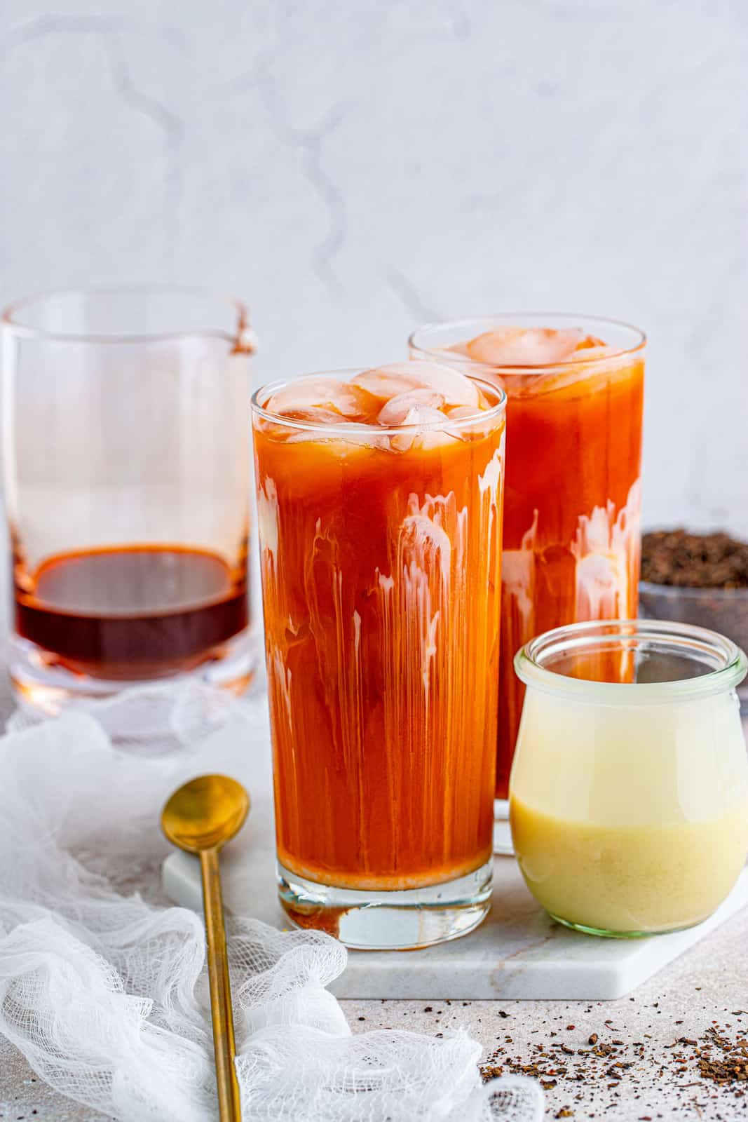 Thai Iced Tea in glasses with spoon and sweetened condensed milk