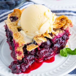Square image of slice of The Best Blueberry Pie Recipe on white plate with ice cream