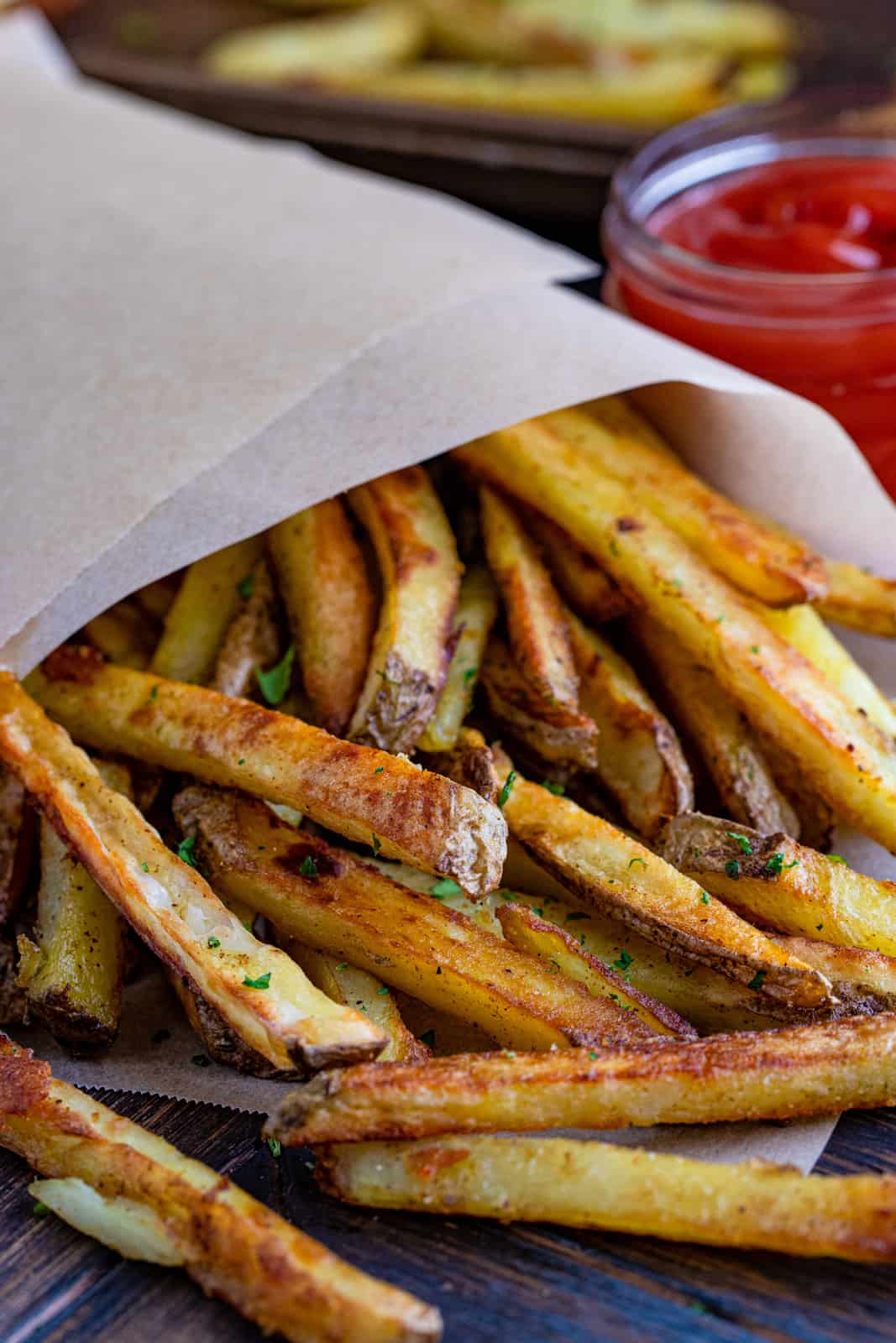 Parchment paper wrapped Baked French Fries close up showing parsley