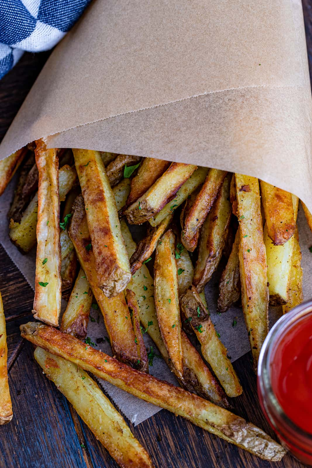 Overhead image of Fries in parchment paper with ketchup
