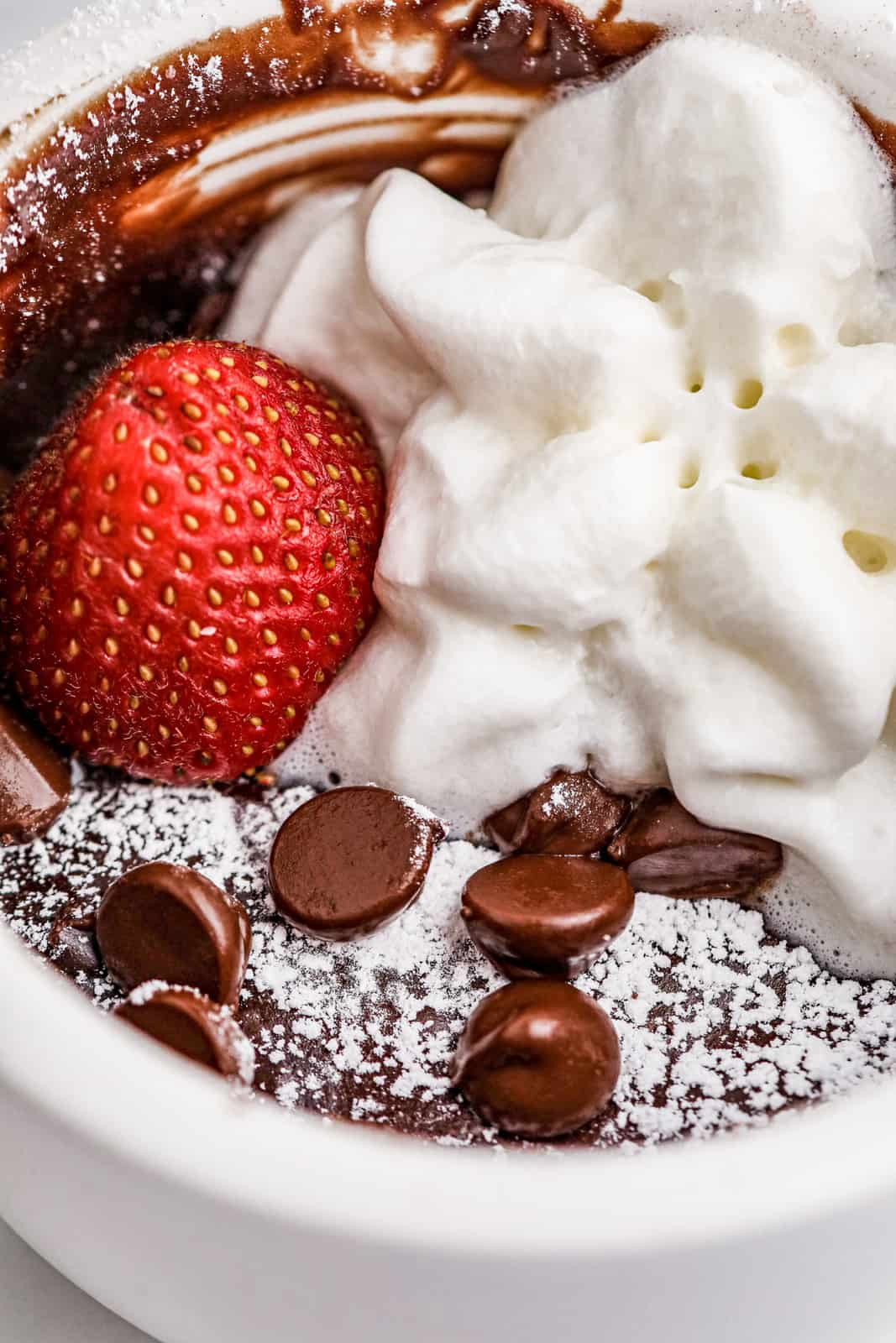 Very close up of Brownie in a Mug with powdered sugar, strawberry and whipped cream