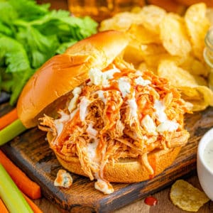Square image of Buffalo Chicken Sandwiches on bun with hot sauce, ranch and blue cheese