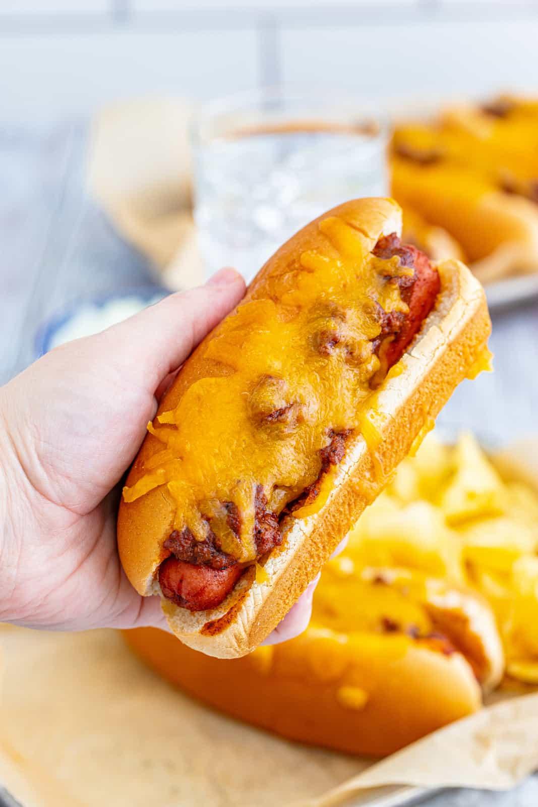 Hand holding up one Chili Dog