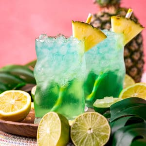 Square image of two drinks I glass with straw and pineapple
