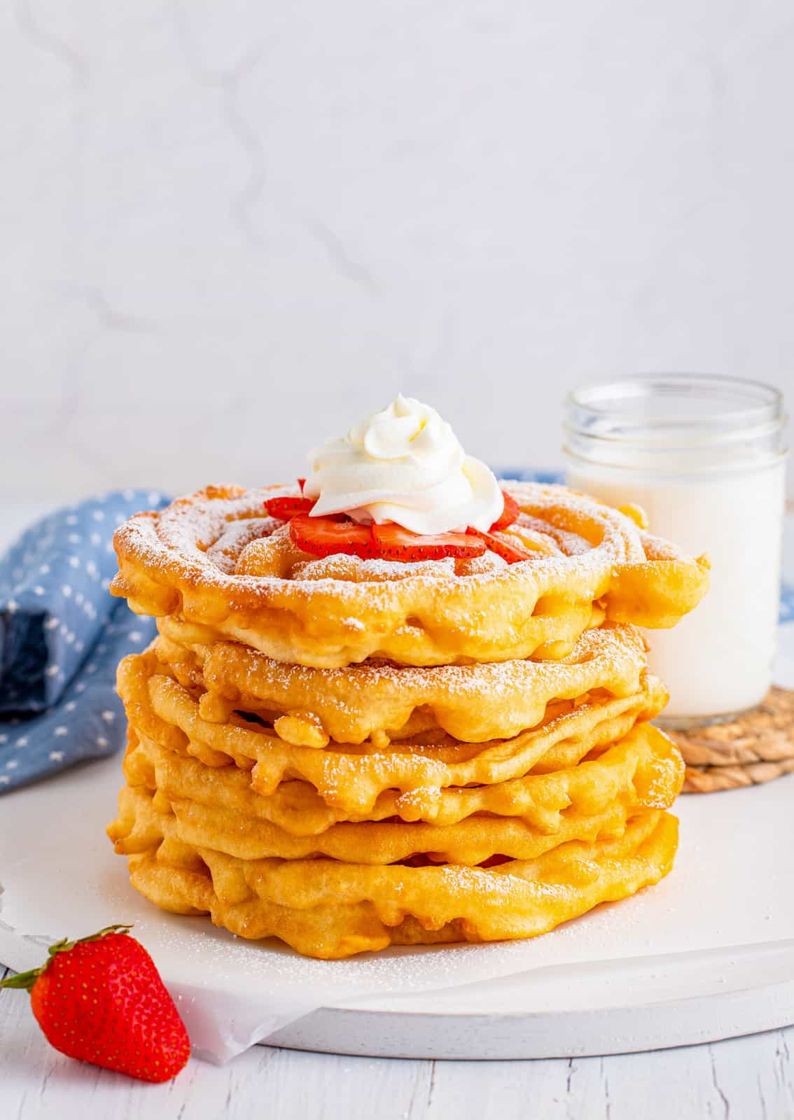 Stacked Funnel Cakes with powdered sugar, strawberries and whipped cream