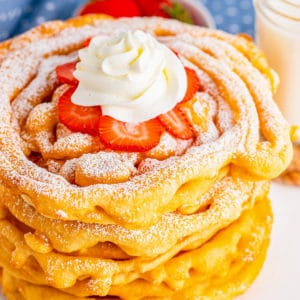 Close up of stacked Funnel Cake Recipe with strawberries, powdered sugar and whipped cream square image