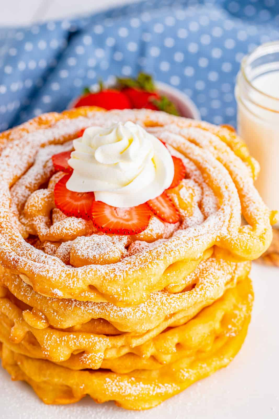 Stacked Funnel Cake Recipe showing top funnel cake topped with Strawberries, powdered sugar and whipped cream