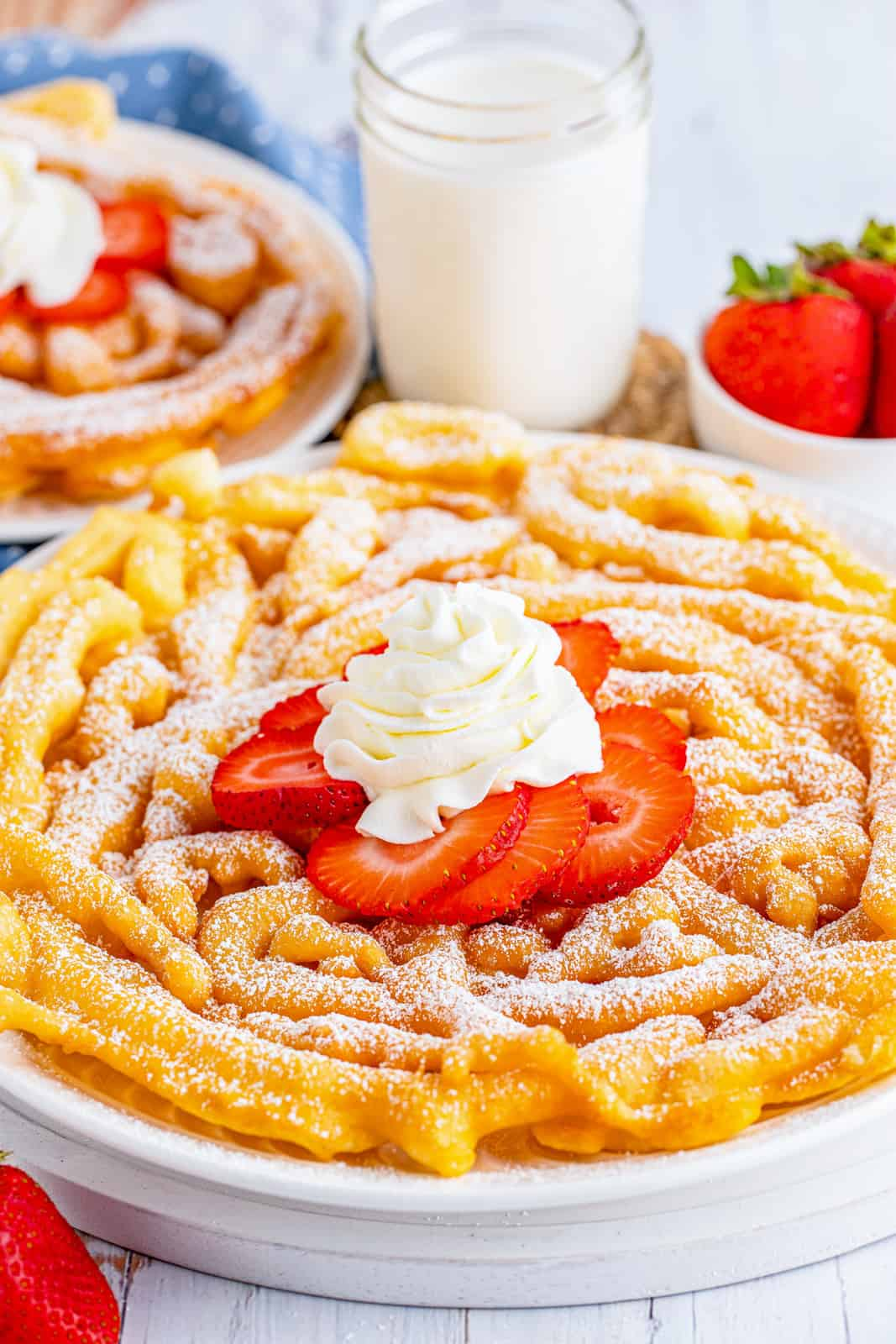 Garnished Funnel Cake Recipe on white plate with milk in background