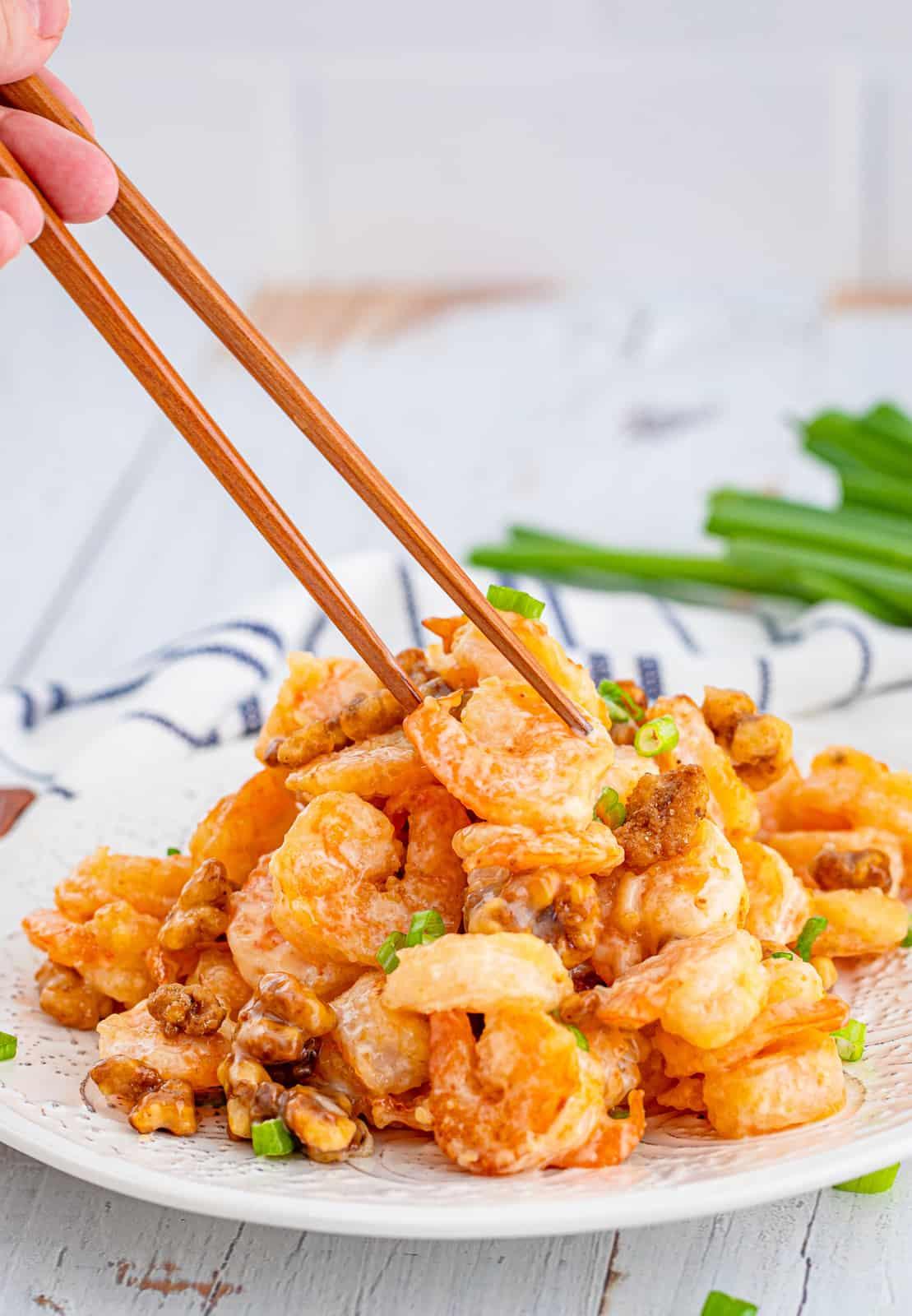 Chop sticks reaching to pick up a piece of Honey Walnut Shrimp Recipe
