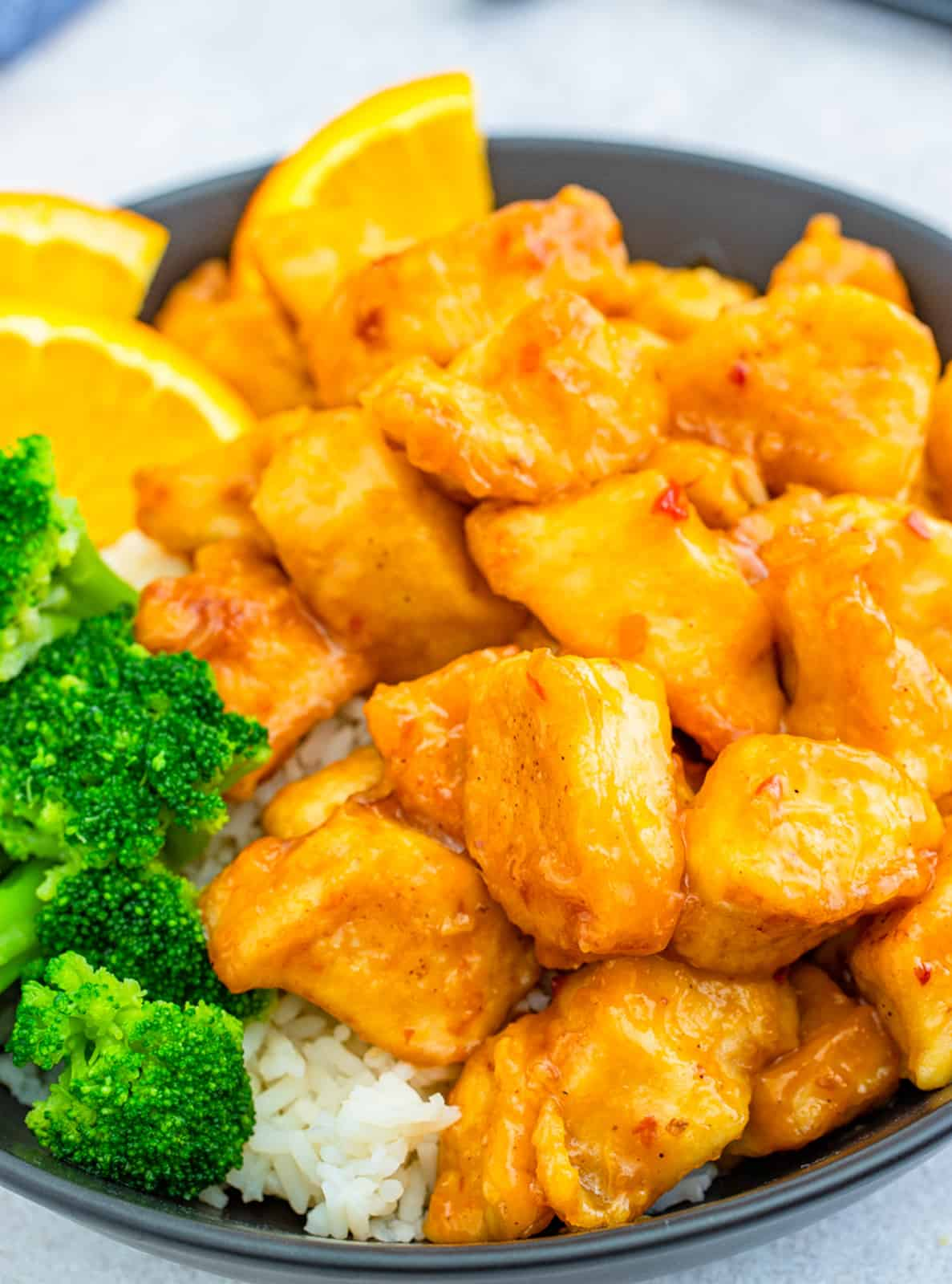 Close up of Orange Chicken on black plate with side dishes