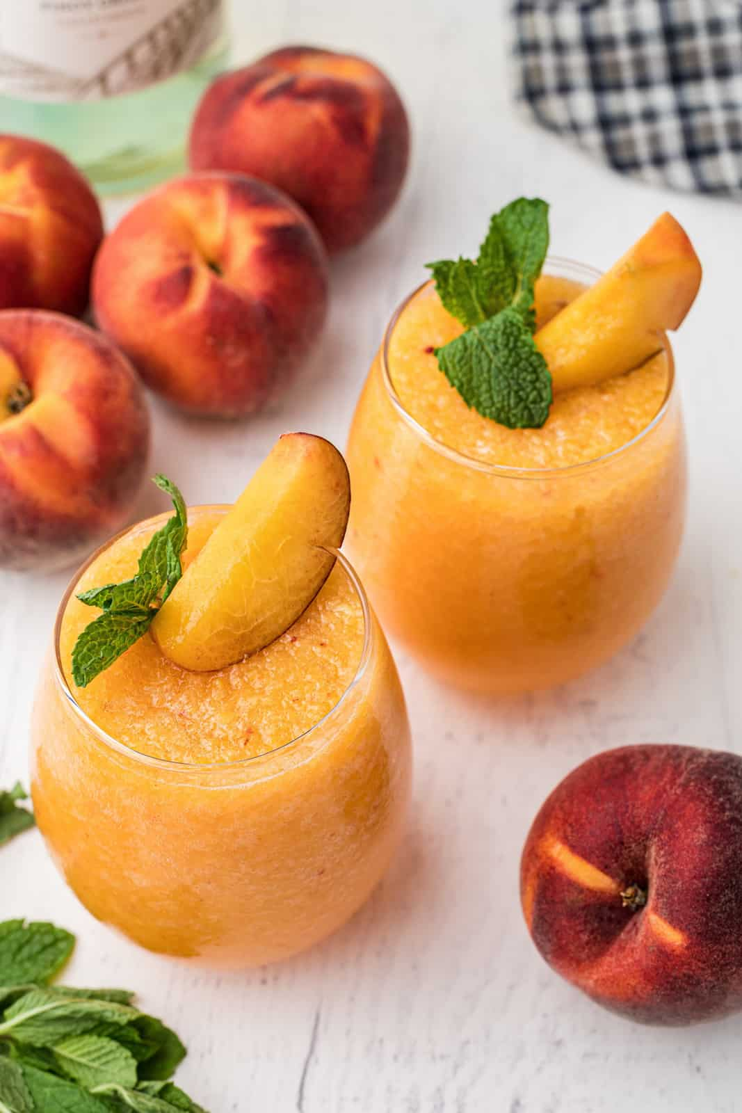 Overhead of two glasses of Peach Wine Slushies with peaches and mint garnish
