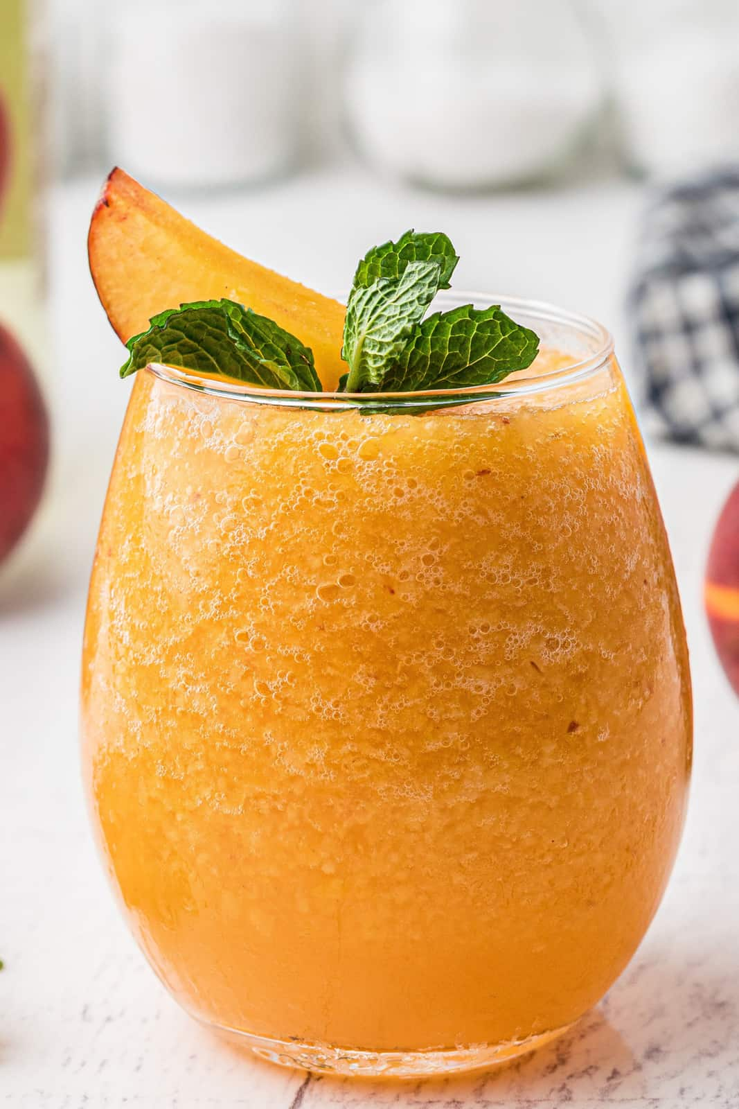 Close up of one slushie with mint and peach garnish