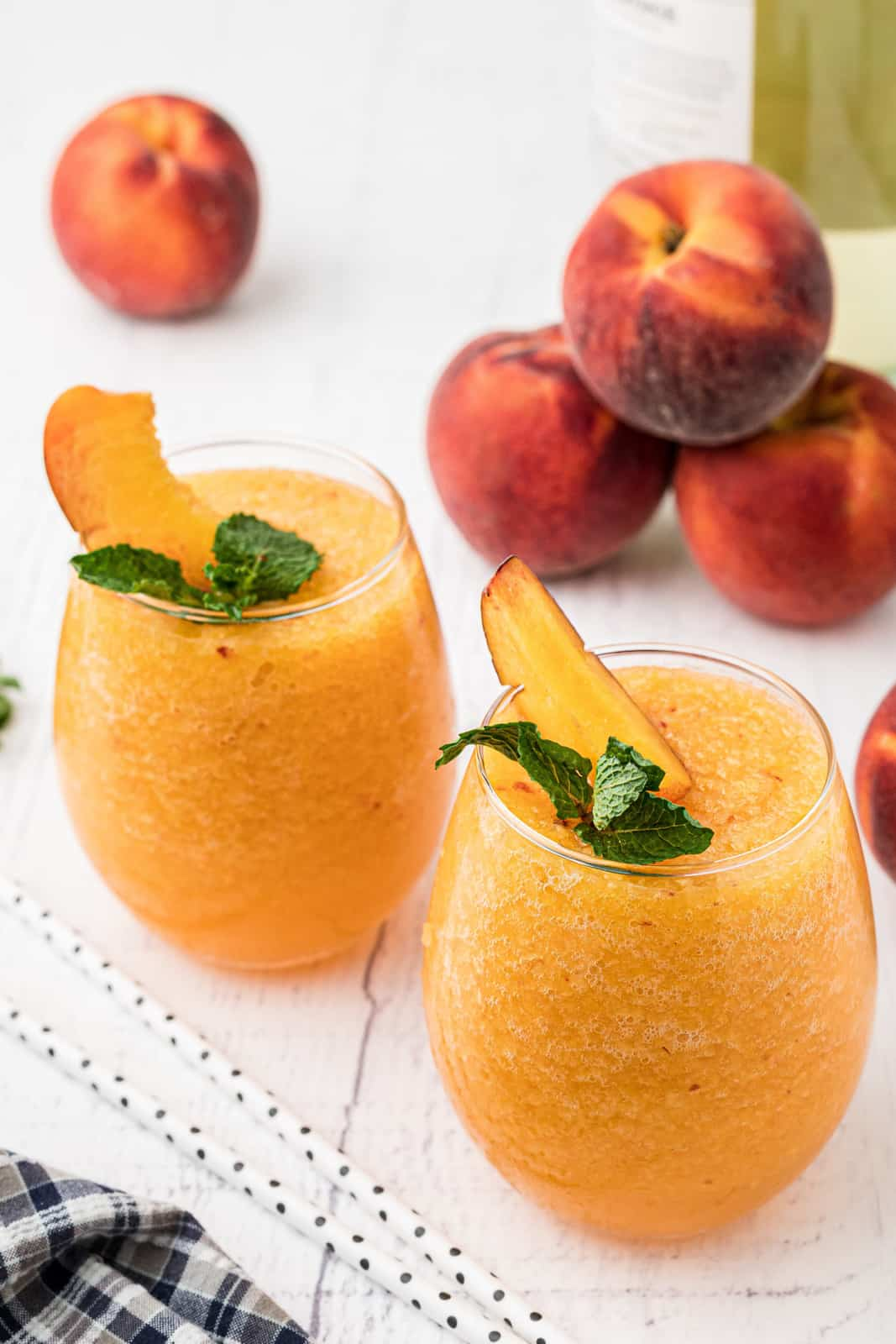 Two Peach Wine Slushies garnished in glasses with fresh peaches in background