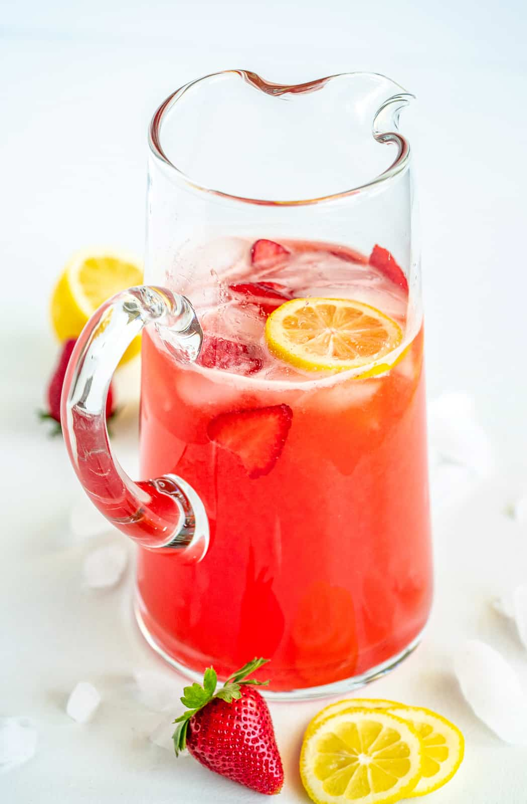 Pitcher of Strawberry Lemonade Recipe with lemons and strawberries