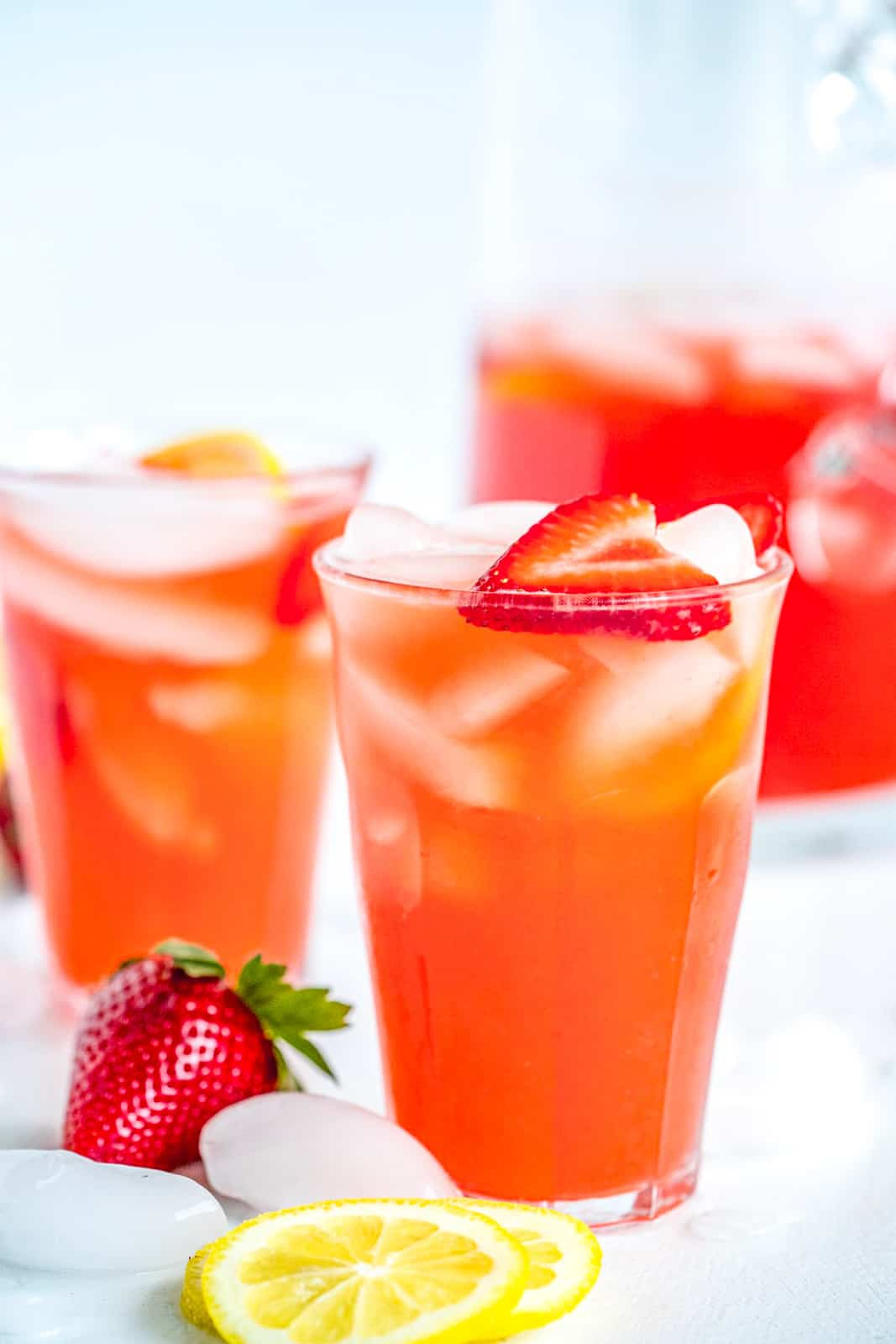 Close up of two classes of Strawberry lemonade garnish with strawberries and lemons
