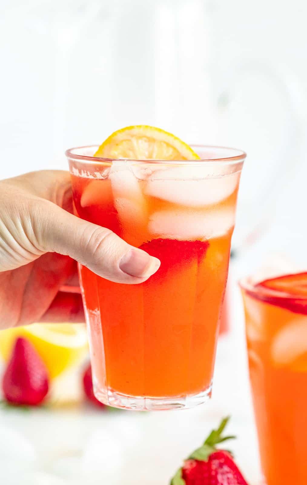 Hand holding up one glass of lemonade