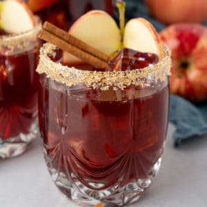 Square photos of glass of Apple Cider Sangria with garnishes.