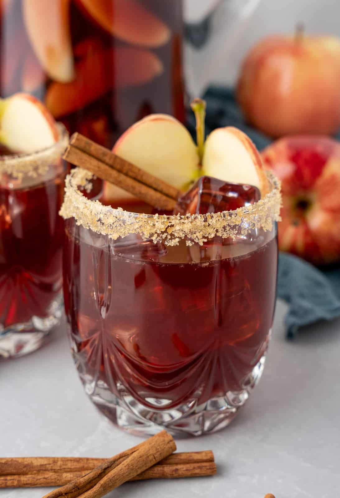 Glass of Apple Cider Sangria with apple slice and cinnamon stick.