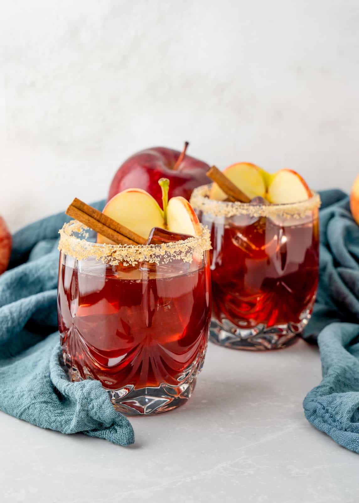 Far away glasses of Apple Cider Sangria Recipe garnished with brown sugar rim and apples and cinnamon sticks.