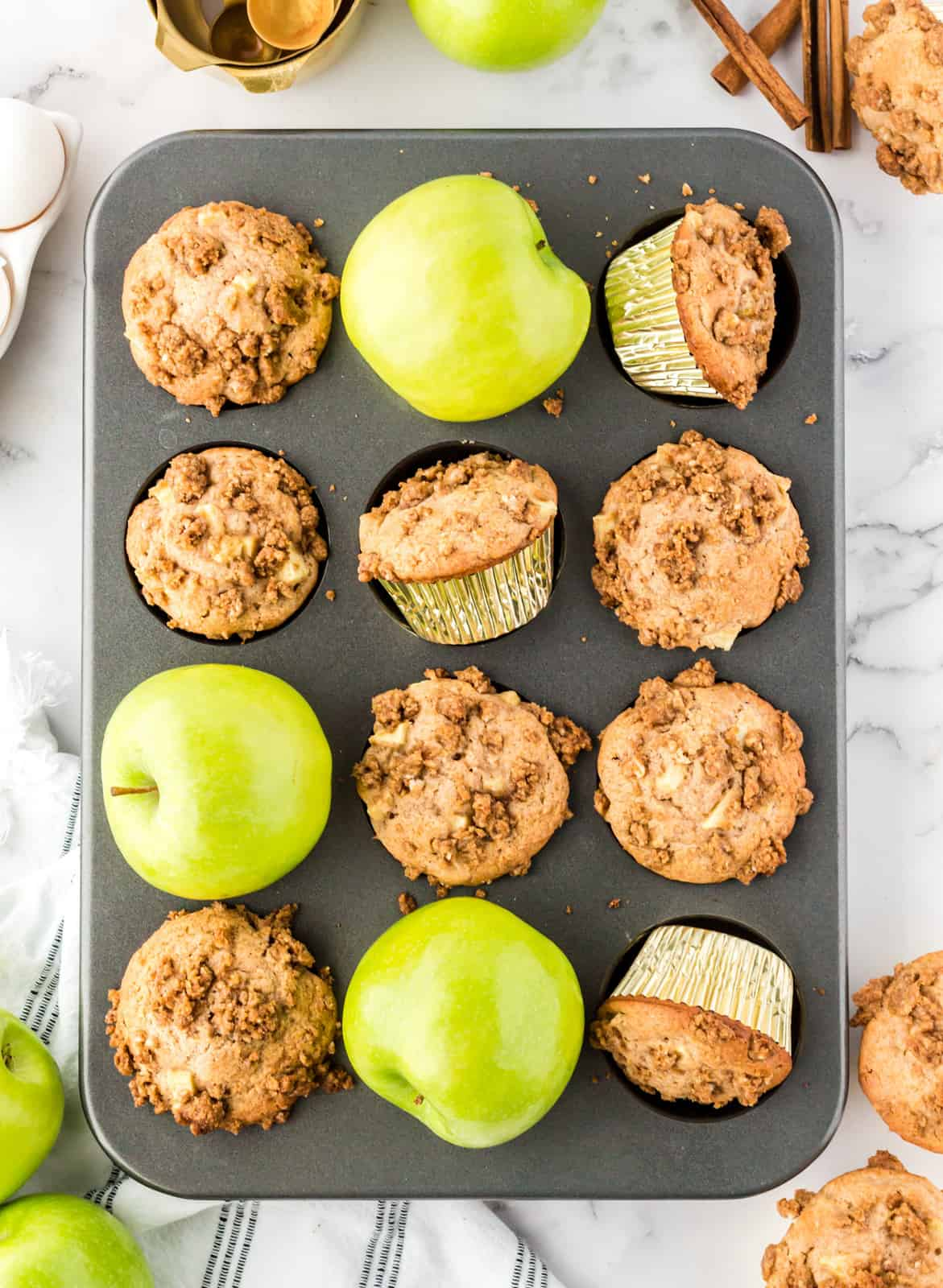 Finished muffins with apples in muffin tin.