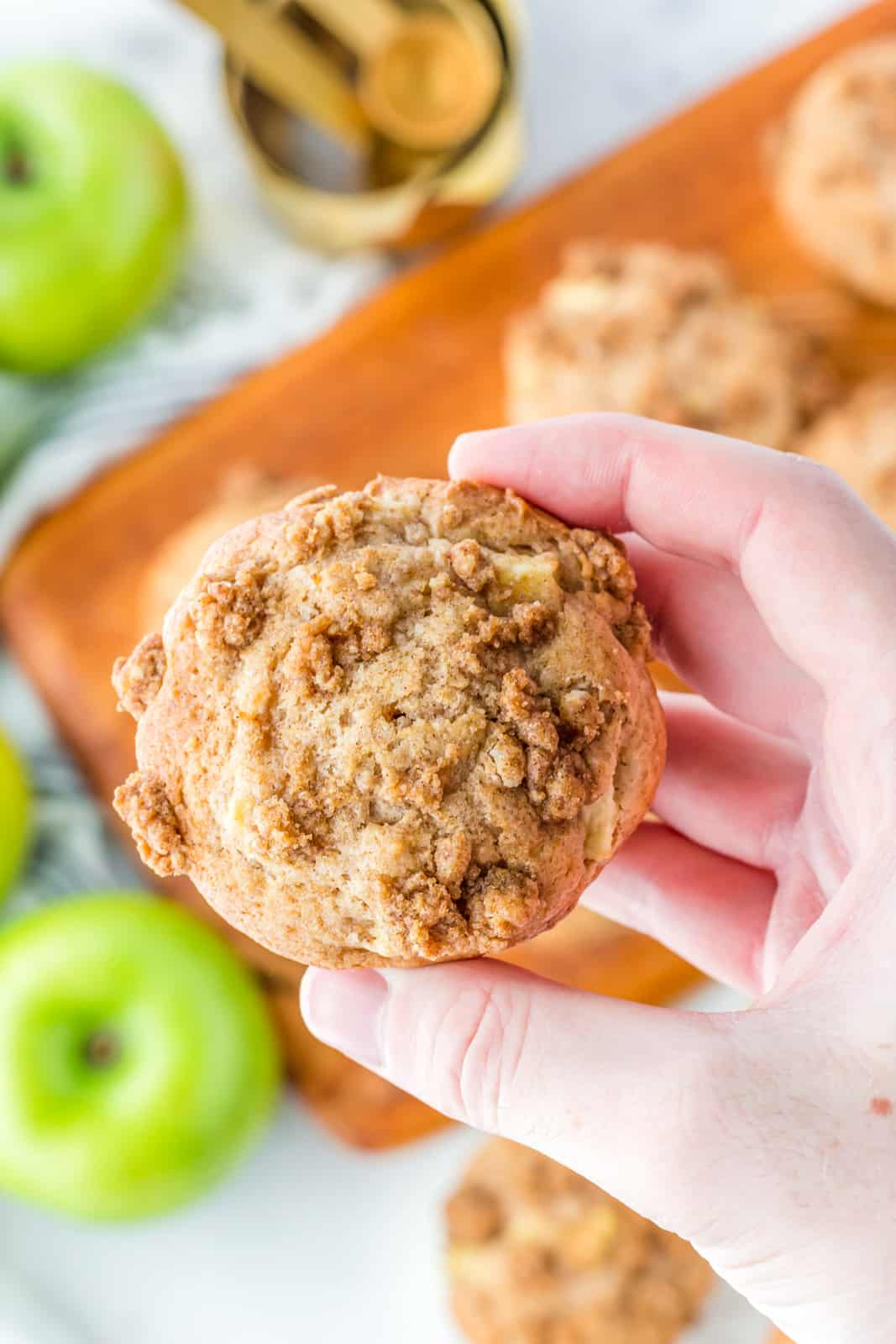 Hand holding up one Apple Cinnamon Muffin showing topping.