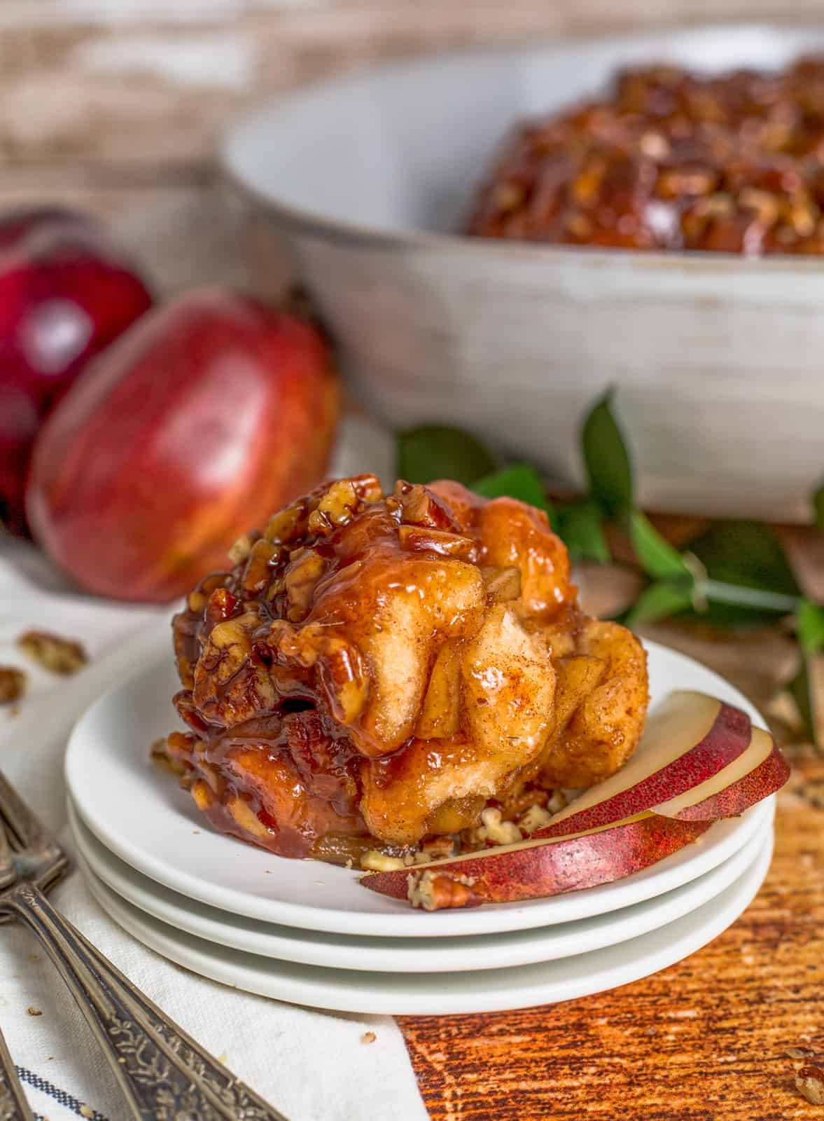 Apple Monkey Bread portion on white plate with slices of apples