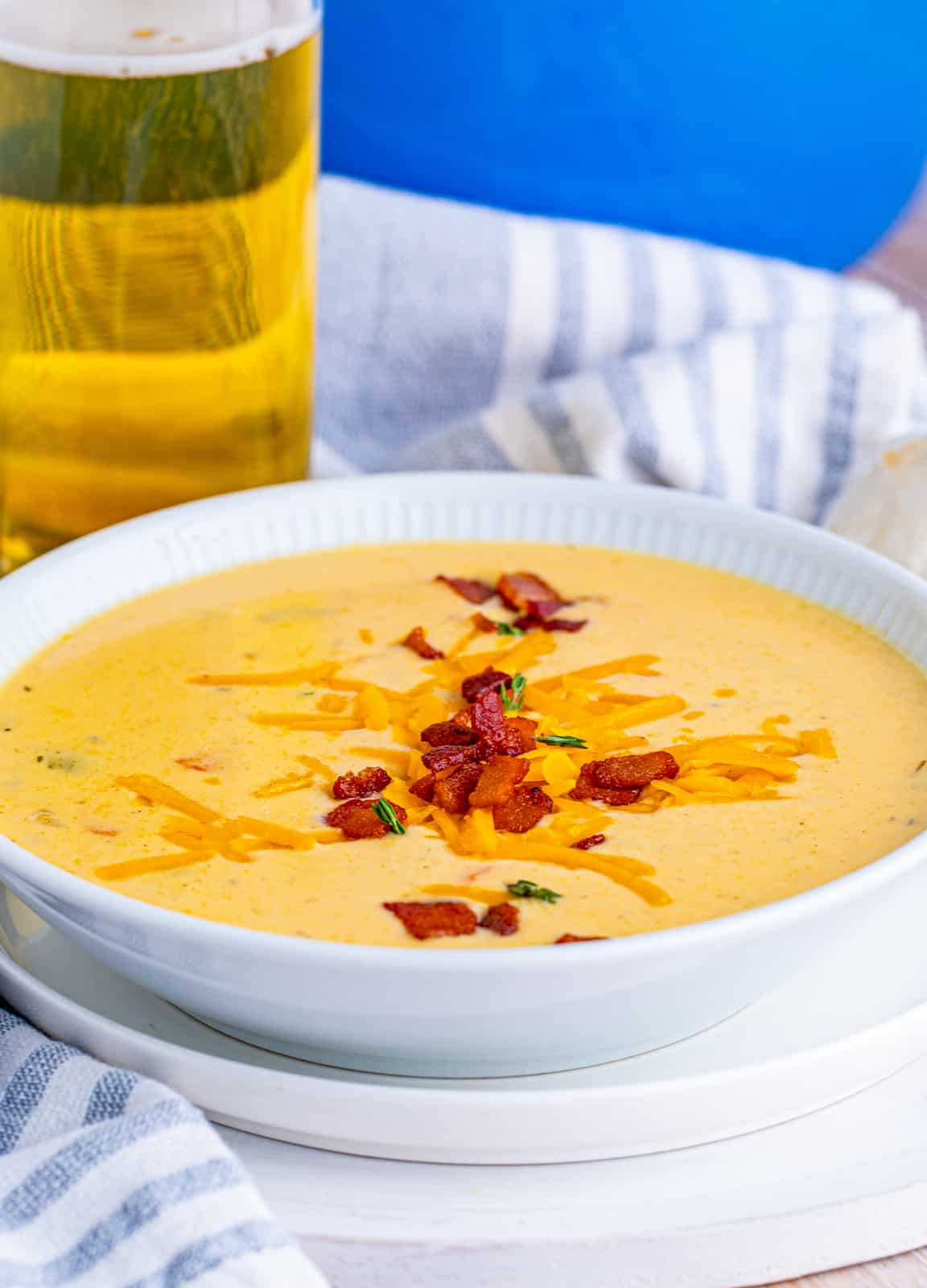 White bowl of Beer Cheese Soup with glass of beer in background.