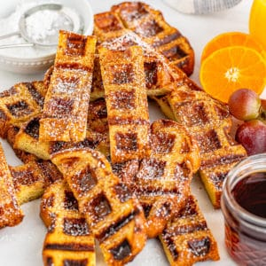 Square image of French Toast Waffle Sticks in pie with syrup and oranges.