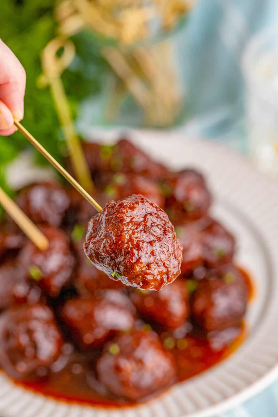 Hand holding up one Grape Jelly Meatball on toothpick.