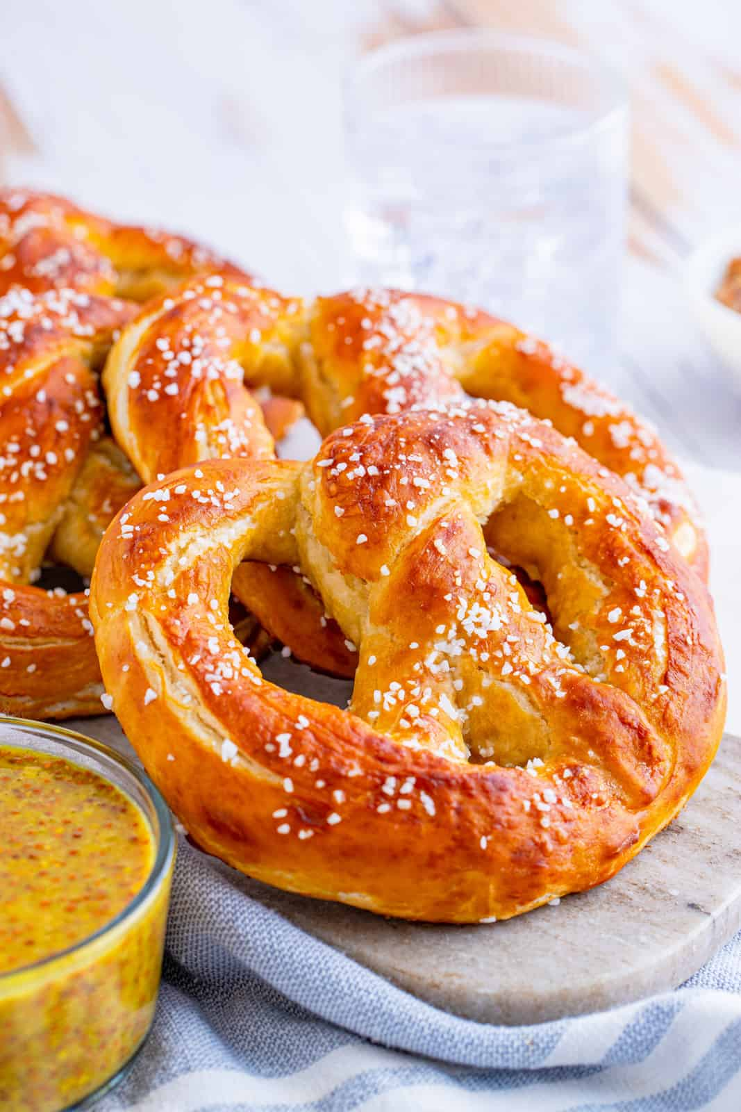 Soft Pretzels laying atop one another on marble board with mustard next to is