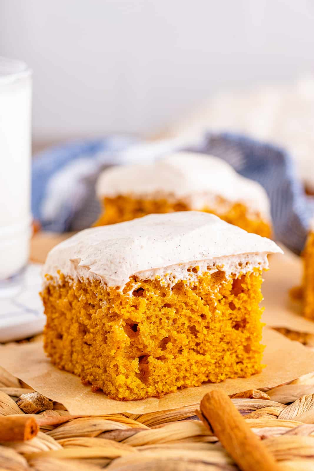 Pumpkin Bars with cinnamon stick and milk in background.