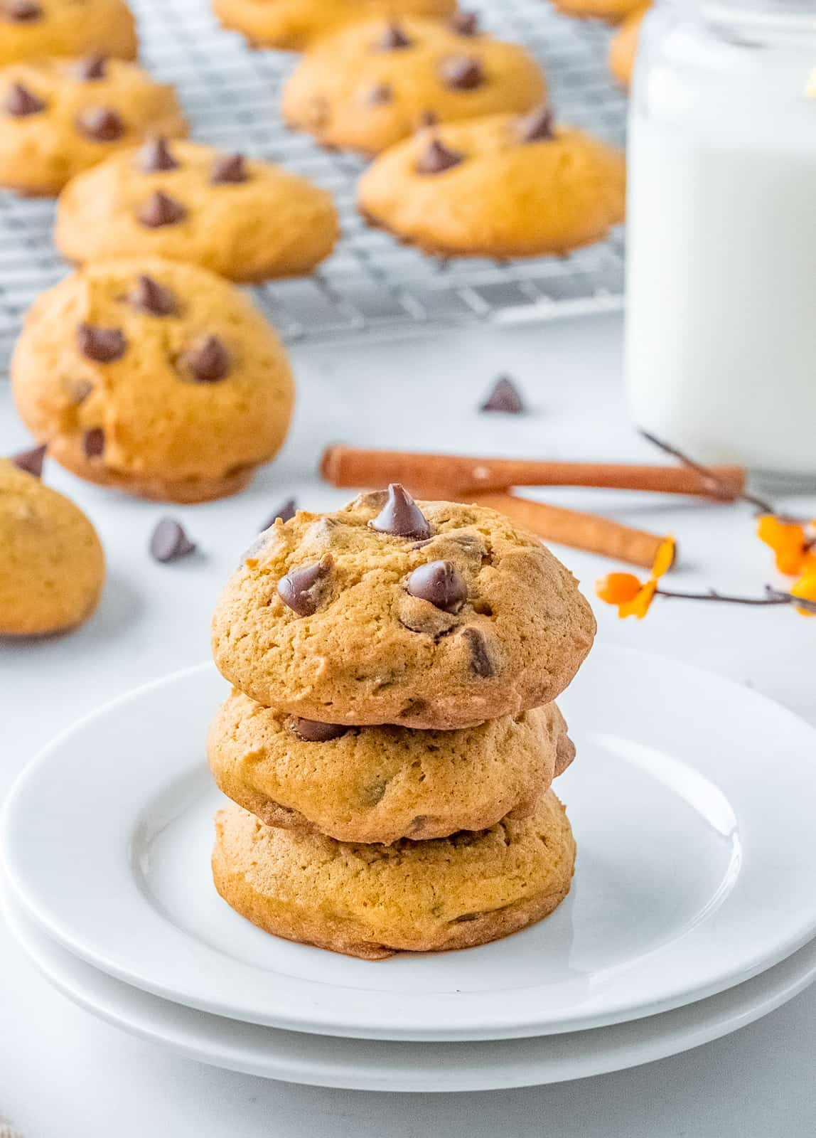 Three stacked Pumpkin Chocolate Chip Cookies on plates.