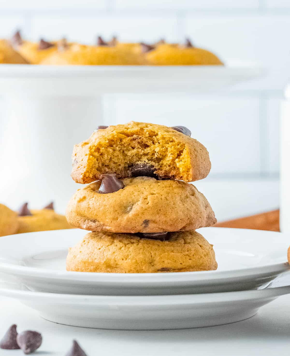 Three stacked Pumpkin Chocolate Chip Cookies on plate with bite taken out of top cookie.