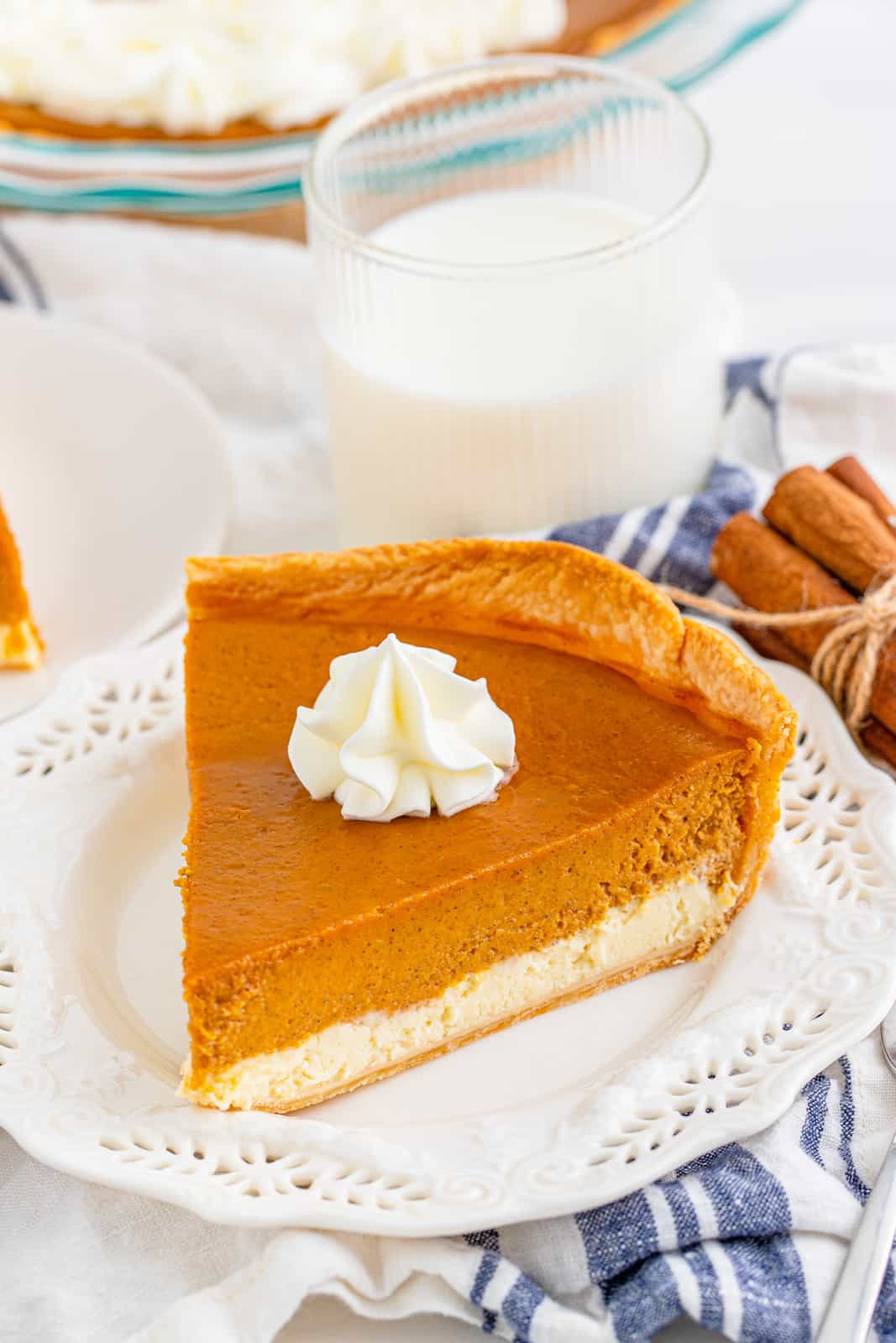 Slice of Pumpkin Cheesecake Pie on white plate with a dollop of whipped cream.