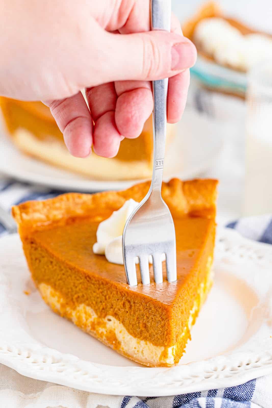 Fork going into slice of Pumpkin Cheesecake Pie.