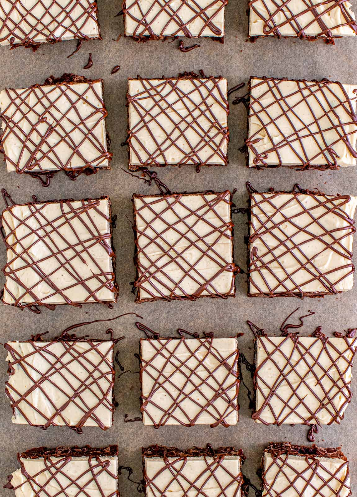 Overhead of cut brownies drizzle with chocolate.